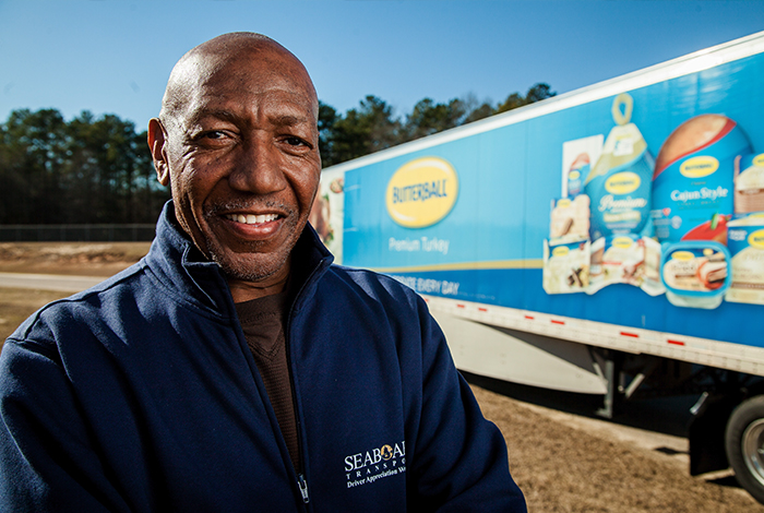 An employee in front of a distribution truck